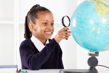 primary schoolgirl looking at globe using a magnifying glass photo