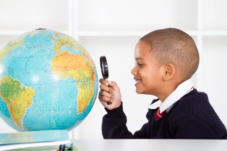 primary schoolboy using magnifying glass looking at globe photo