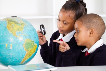 uniform student: two elementary school students looking at globe