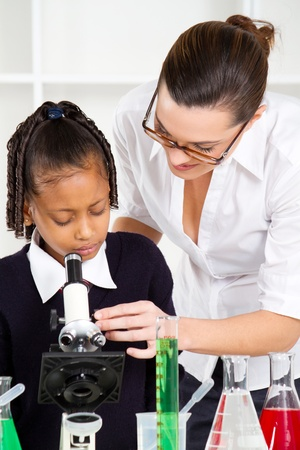 friendly teacher helping primary schoolgirl in science class photo