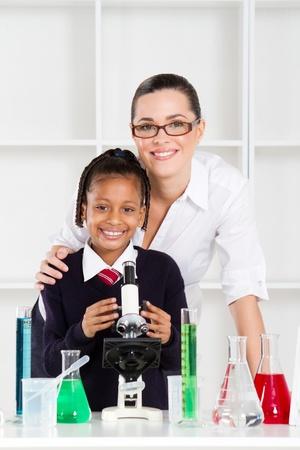 portrait of beautiful science teacher and schoolgirl in lab photo