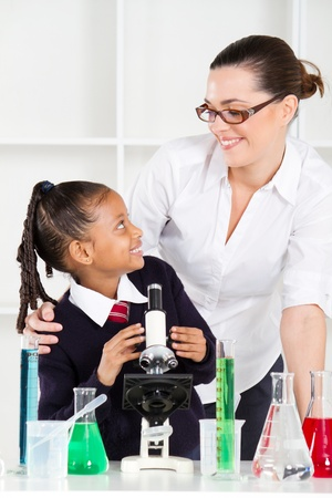 friendly teacher talking to elementary student in science class photo