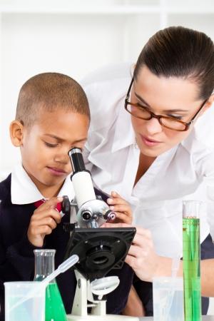 first class: beautiful young teacher helping school boy in science class