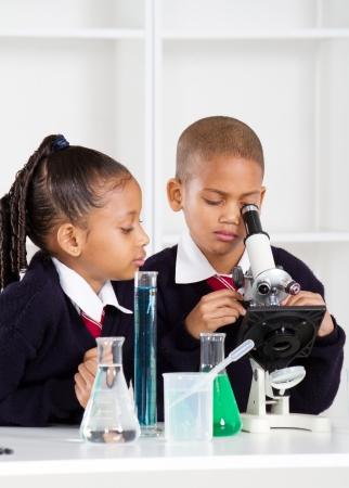 experimento: ni�os de escuela primaria en la clase de Ciencias utilizando un microscopio Foto de archivo