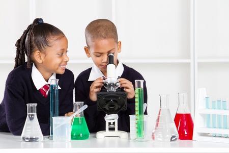 uniforme escolar: niños de escuela primaria en la clase de Ciencias utilizando un microscopio Foto de archivo