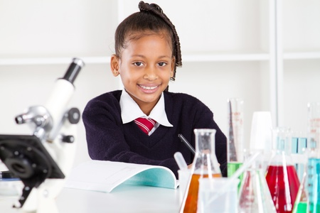 first class: happy female elementary school pupil in science class Stock Photo