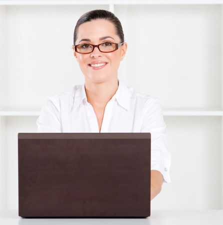good looking young businesswoman sitting in office with laptop photo