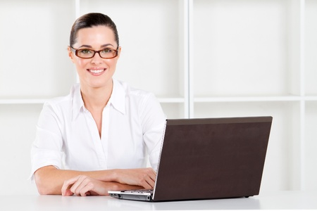 attractive young businesswoman sitting in office with laptop photo