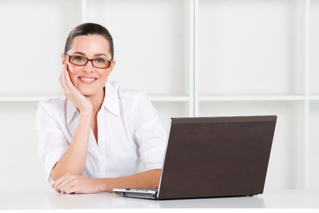 young businesswoman in office with laptop photo