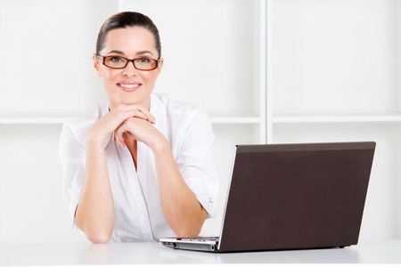 beautiful young businesswoman sitting in office with laptop photo