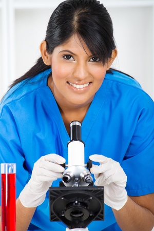 young lab technician using microscope photo