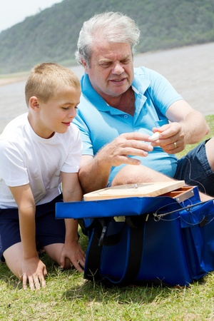 grandpapa: grandfather teaching grandson how to prepare fishing tackles Stock Photo