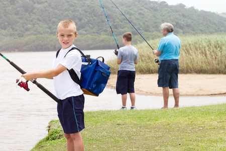 happy little boy fishing with family by the lake photo