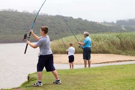 grandpapa: young teenage boy casting a fishing rod, background is his grandfather and little brother fishing Stock Photo