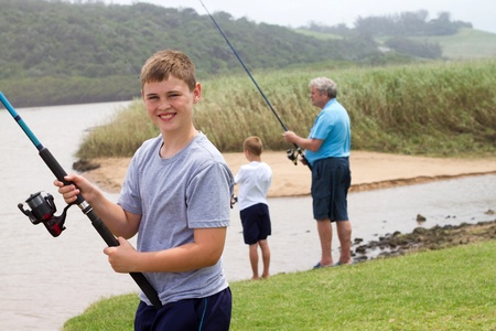 happy teenage boy fishing with grandpa and little brother by the lake photo