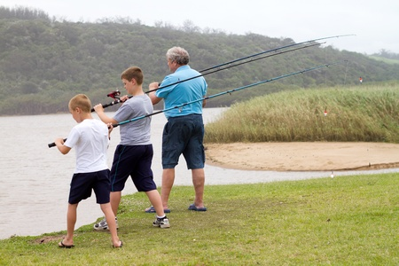 grandpapa: two grandsons fishing with their grandp by the lake