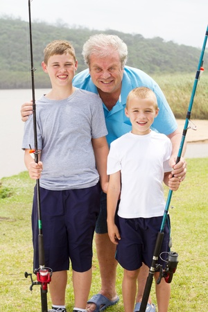 portrait of grandpa and grandsons fishing by the lake photo