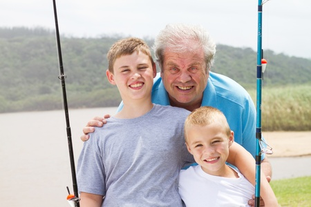 portrait of grandpa and grandsons with fishing rods photo