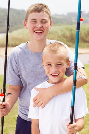 portrait of two little boys fishing by the lake photo