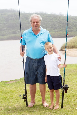 portrait of grandfather and grandson standing by lake with fishing rods photo
