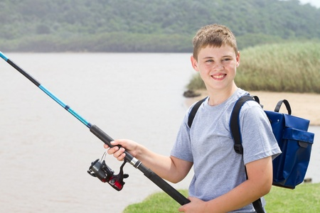 young teenage boy fishing by the lake photo