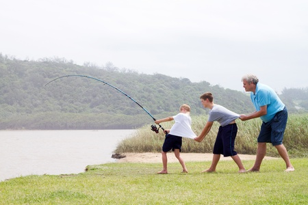grandsons: grandpa and grandsons together pulling a big fish out of water with fishing rod Stock Photo