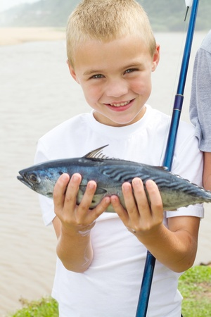 happy little boy showing a fish he just caught photo