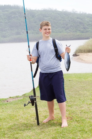 happy teen boy holding fishing rod and a fish he caught photo