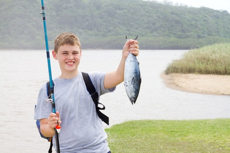 fish pond: happy teen boy showing a fishing he just caught