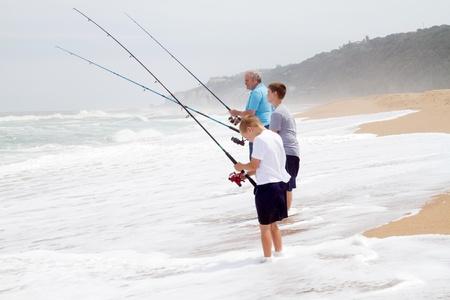 hombre pescando: abuelo y nieto de pesca en la playa Foto de archivo