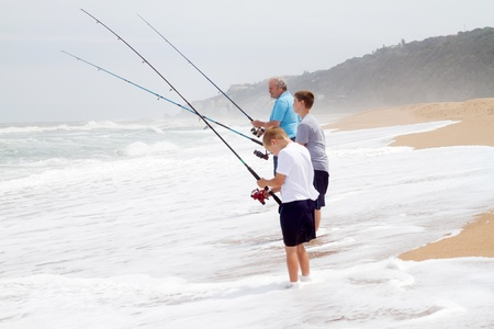 family activities: grandpa and grandsons fishing on beach
