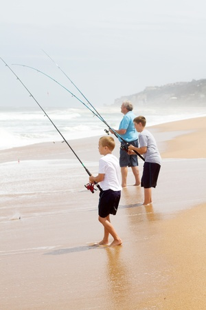 grandpapa: grandfather and two grandsons fishing on beach Stock Photo