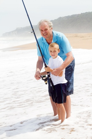 grandpa teaching grandson fishing on the beach photo