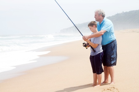 grandpapa: grandfather teaching teen grandson fishing on beach Stock Photo