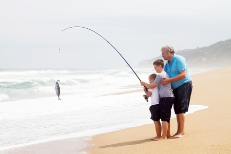 large family: grandpa and two grandsons together pulling a fish out of water with fishing rod on beach