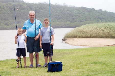 grandpapa: grandfather and grandsons fishing by the lake Stock Photo