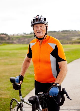 senior professional male cyclist with his road bike photo