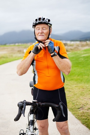 vestidos antiguos: hombre mayor poniendo su casco de ciclismo antes de montar a caballo