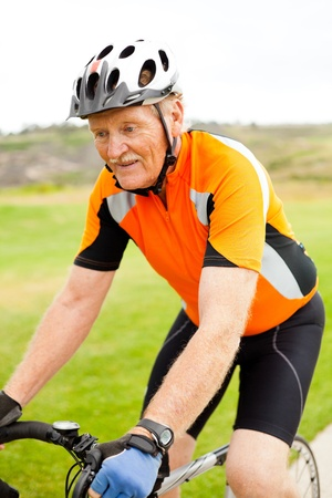 bicyclists: happy healthy senior man riding bicycle Stock Photo