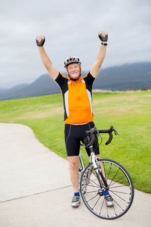 cheerful active senior man on bicycle with arms up photo