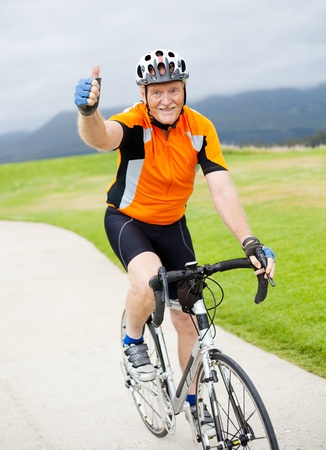happy senior male bicyclist giving thumb up on bicycle Stock Photo