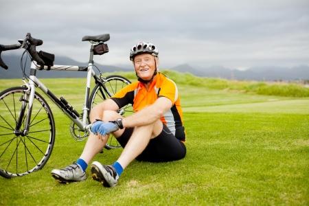 felice ciclista anziano seduto sull'erba riposo Archivio Fotografico