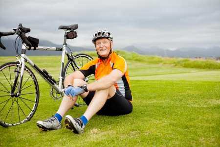 elderly exercise: happy senior cyclist sitting on grass resting
