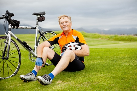 active senior bicyclist taking a break on the hill photo