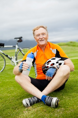 happy active senior bicyclist sitting on grass and resting photo