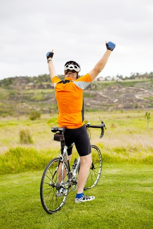 cheerful senior cyclist on top of the mountain Stock Photo
