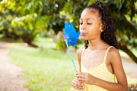 pinwheel: little indian girl blowing on a pinwheel