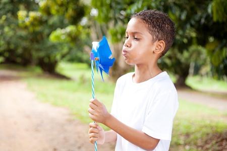 cute little boy blowing on a pinwheel photo