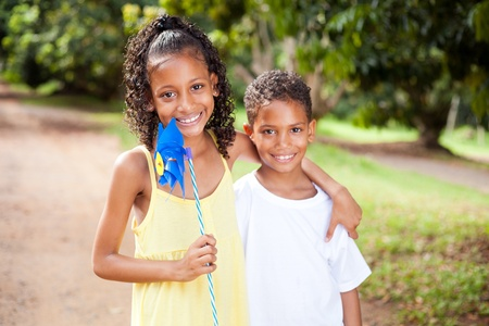 brothers and sisters: happy sister and brother with pinwheel outdoors