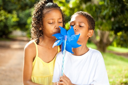 two kids blowing on a pinwheel together photo